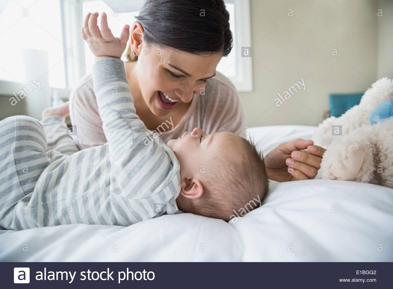 Mutter und Baby Lachen auf Bett Stockbild