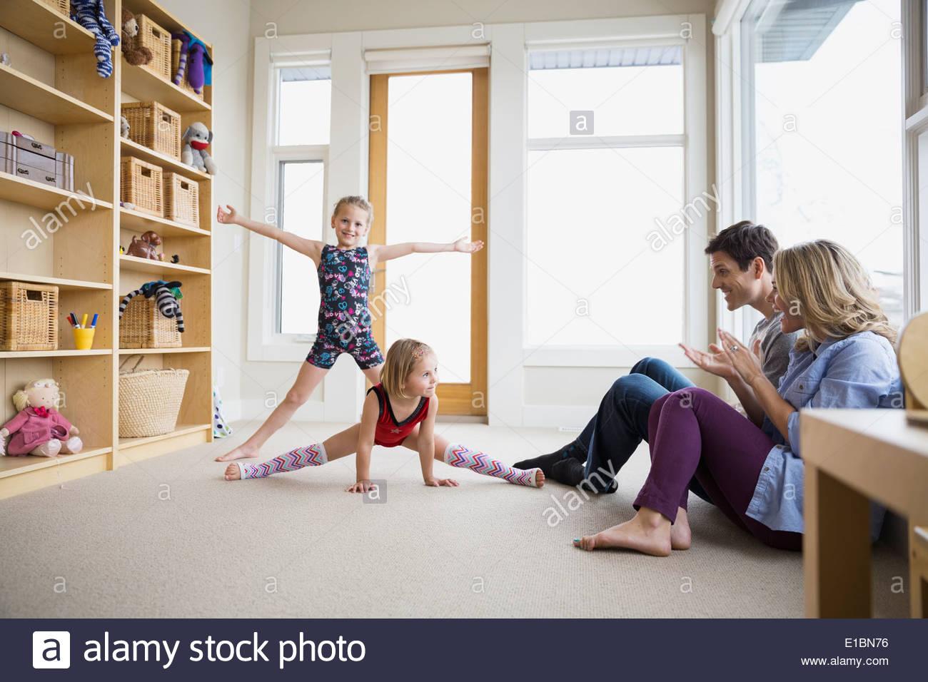 Eltern beobachten Töchter tanzen im Wohnzimmer Stockbild