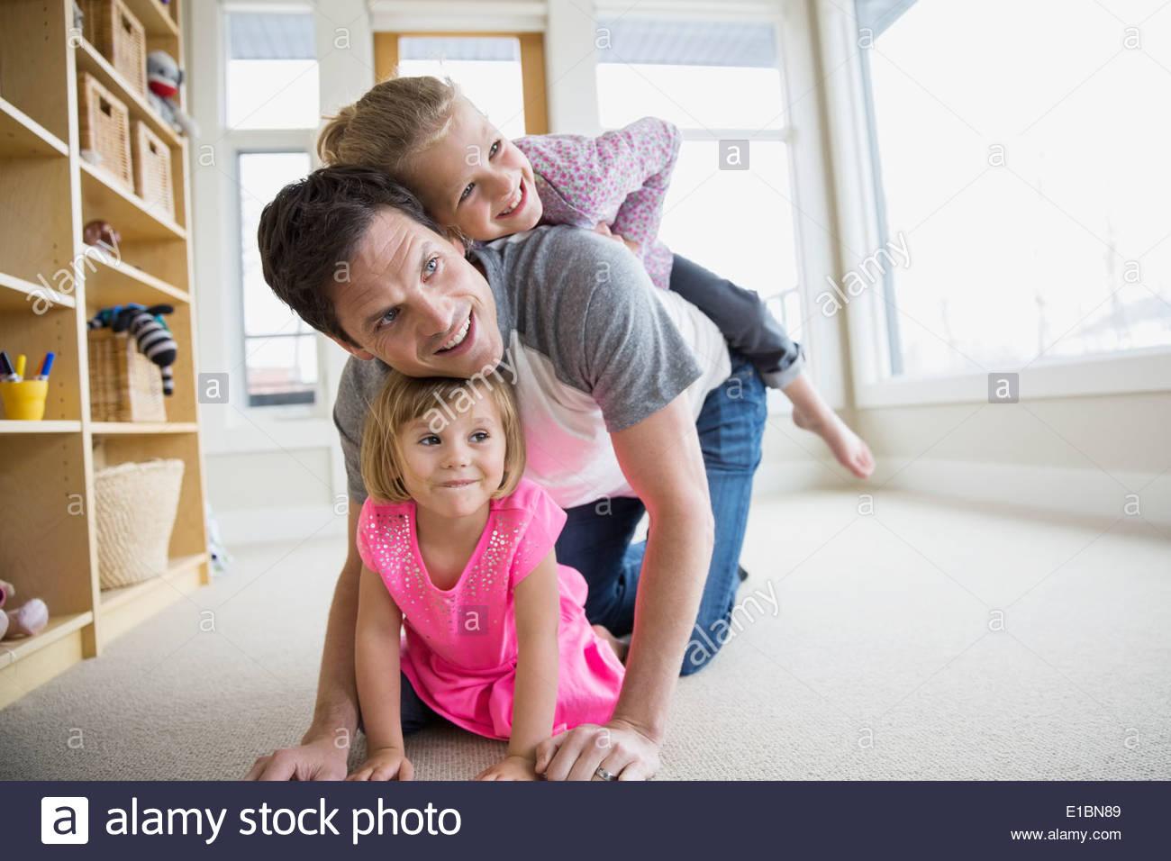 Vater und Töchter spielen im Wohnzimmer Stockbild