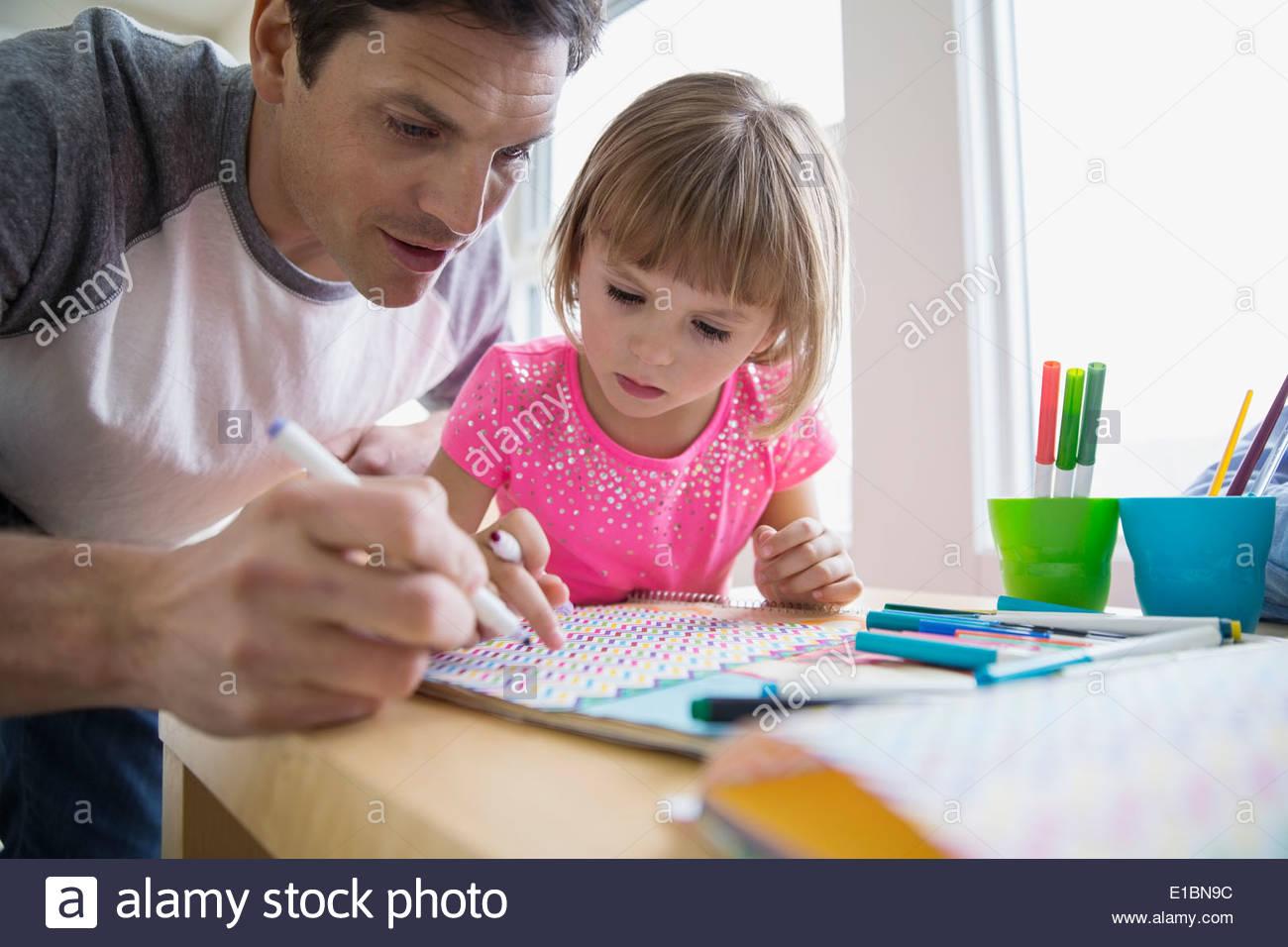 Vater und Tochter machen Papier Handwerk am Tisch Stockbild
