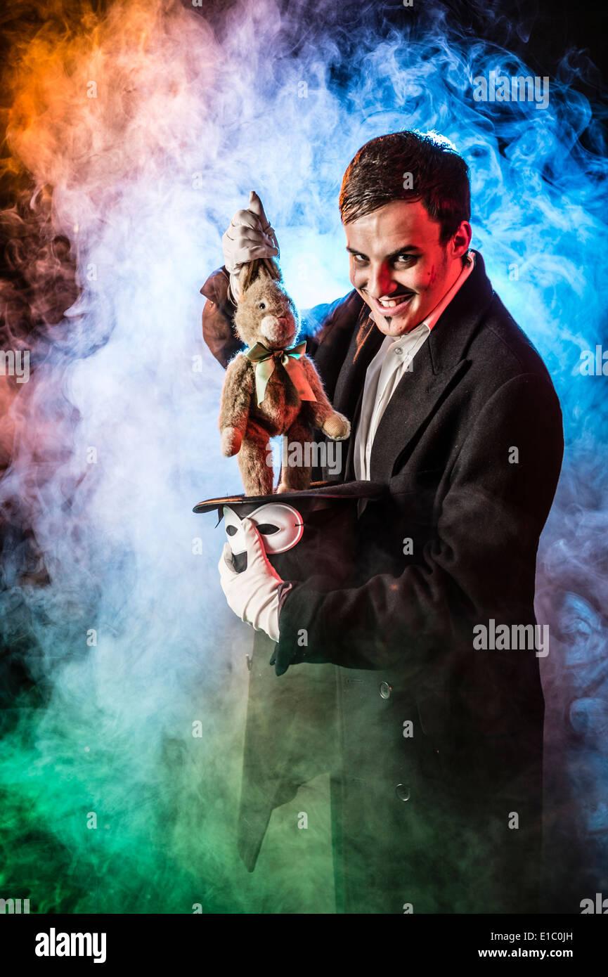 Eine böse finstere schlechte Zauberer bekränzt in Rauch zieht ein Kind Stofftier Kaninchen aus einem Hut Stockbild