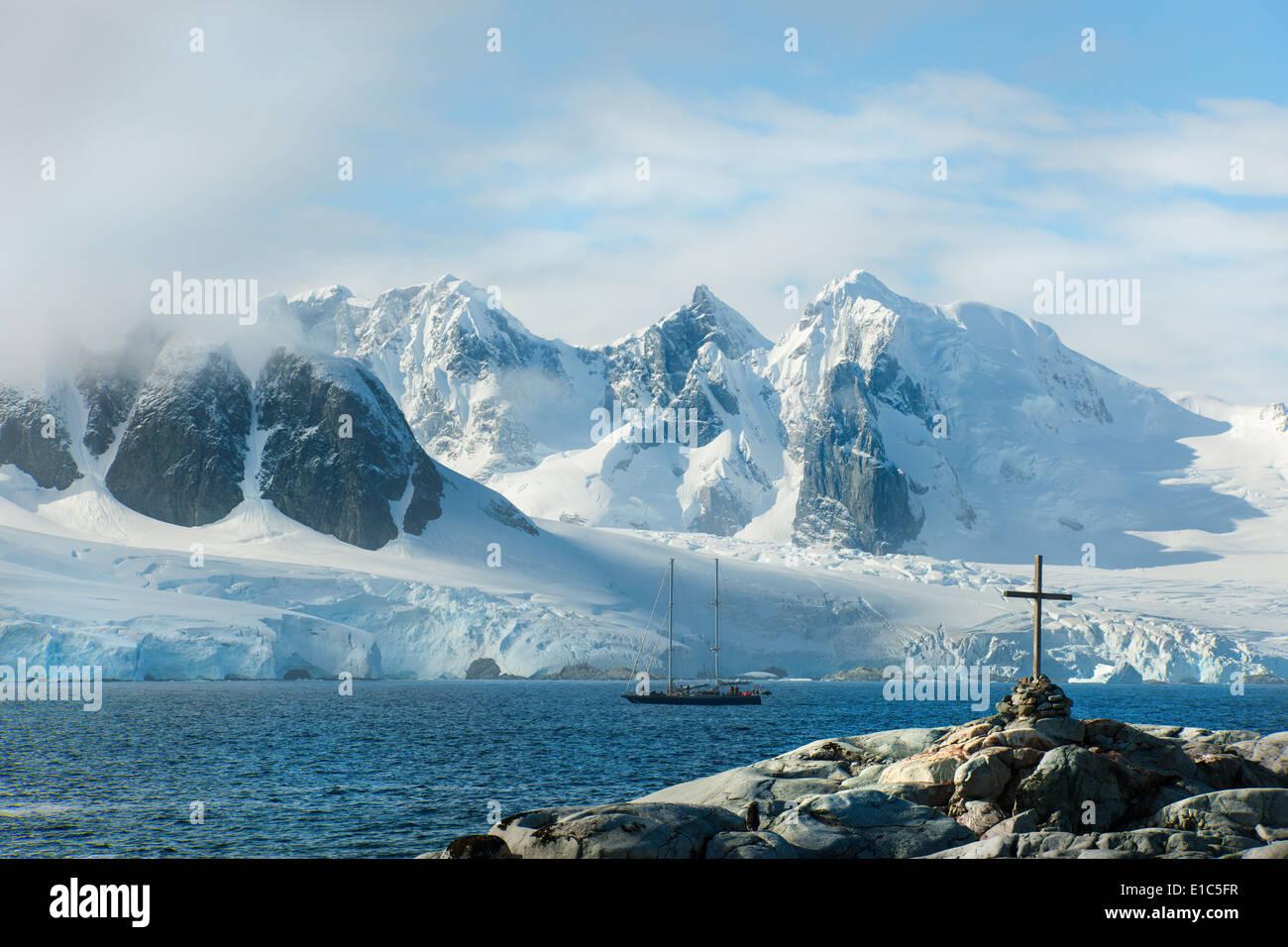 Ein Kreuz und Grab auf einem Hügel auf Petterman Insel. Mast-Großsegler im Kanal. Stockbild