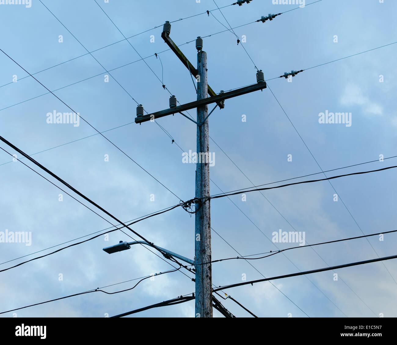 Telefonmast und Stromleitungen von den Boden gegen ein bewölkter Himmel betrachtet. Stockbild