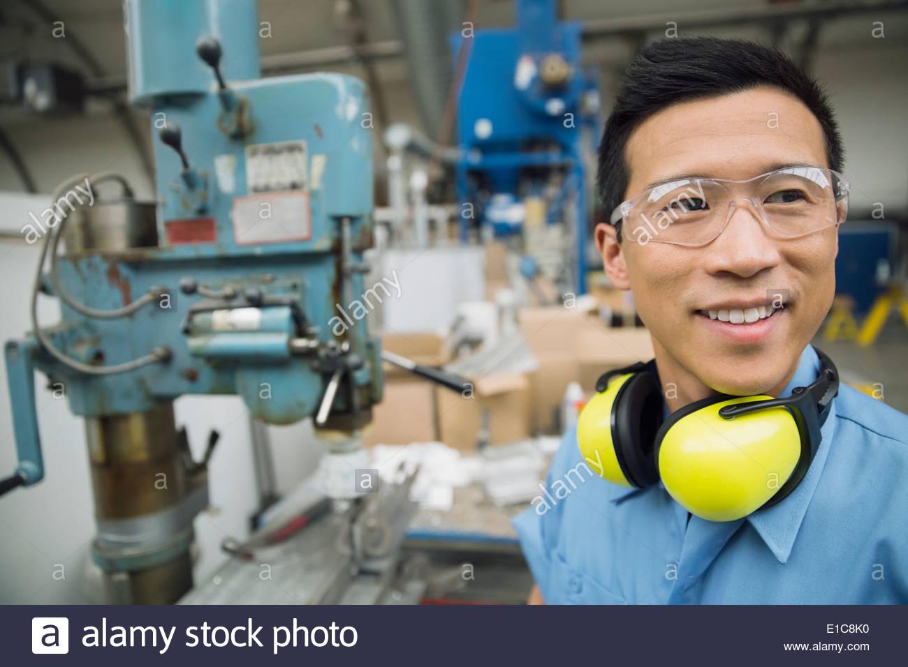 Lächelnde Arbeiter neben Maschinen im Werk Stockbild