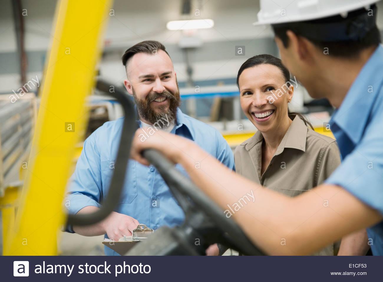 Arbeitnehmer spricht am Gabelstapler Stockbild