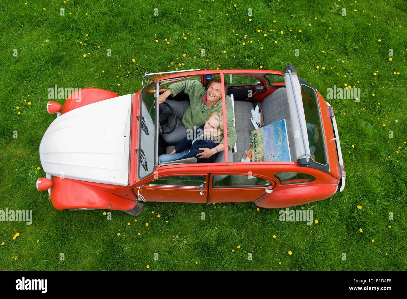 Blick von oben auf zwei Personen, ein paar in einem Auto bei geöffnetem Dach. Stockfoto