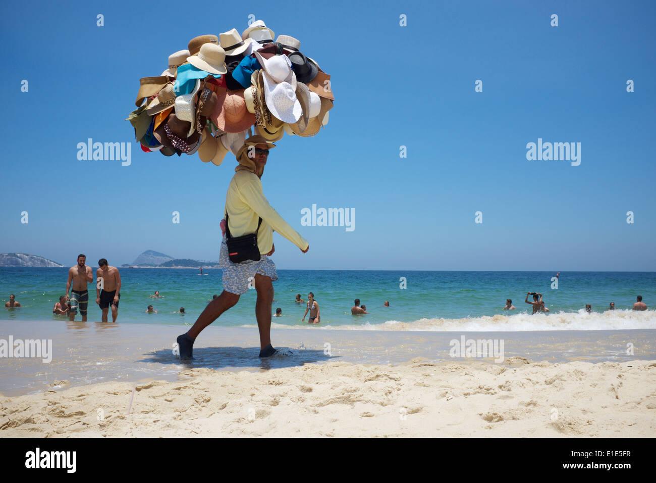 RIO DE JANEIRO, Brasilien - 22. Januar 2014: Spaziergänge am Strand Verkäufer verkaufen Hüte tragen seine Ware am Strand von Ipanema. Stockbild