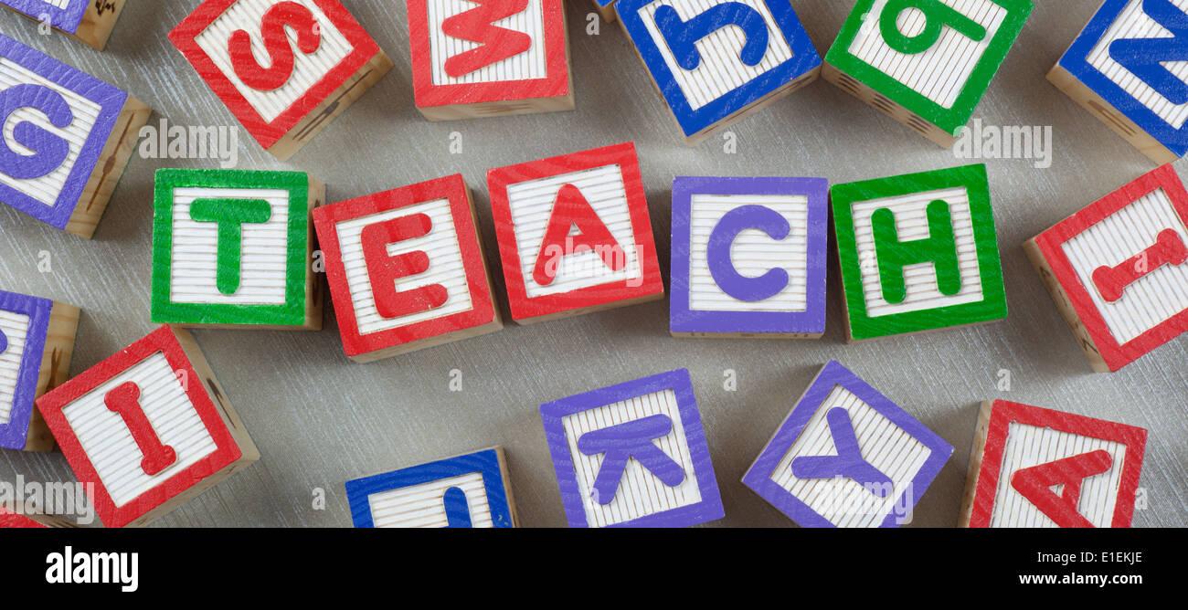 Hölzerne Blöcke bilden das Wort TEACH in der Mitte Stockbild