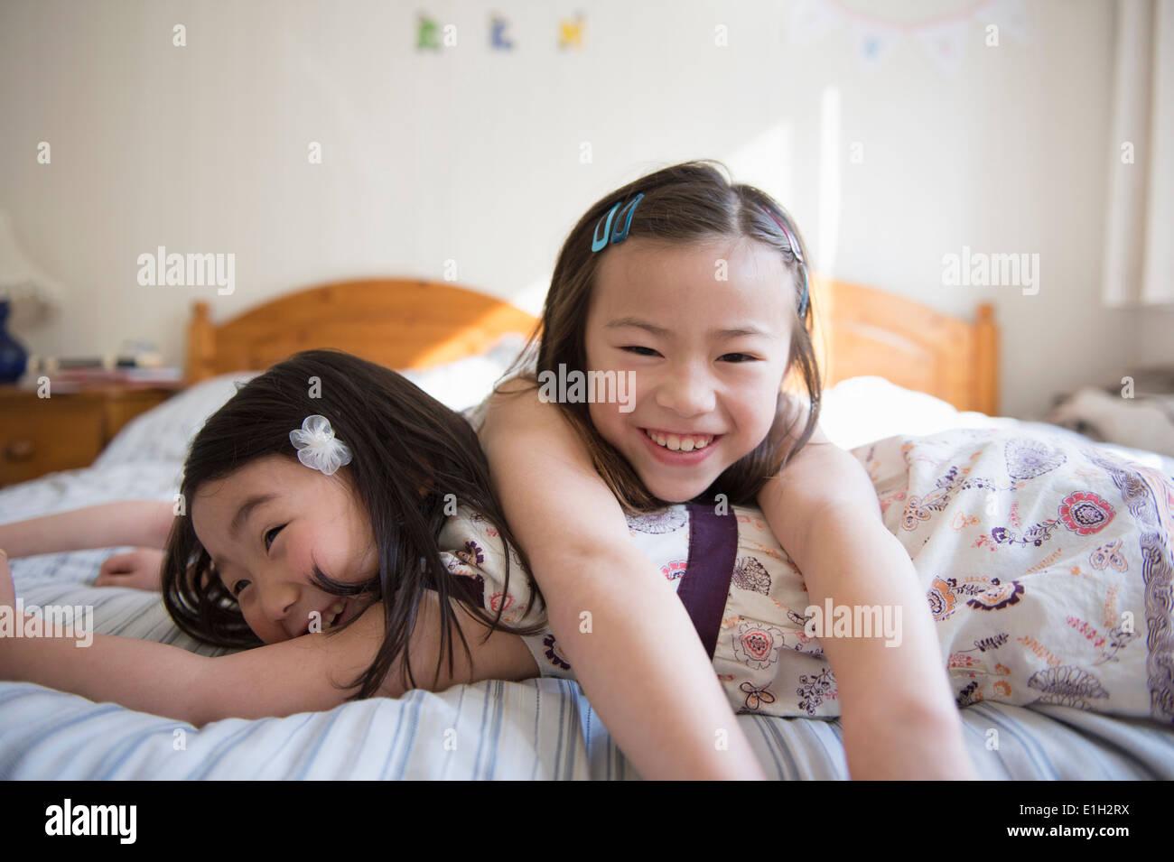 Zwei junge Freundinnen auf Bett liegend Stockfoto
