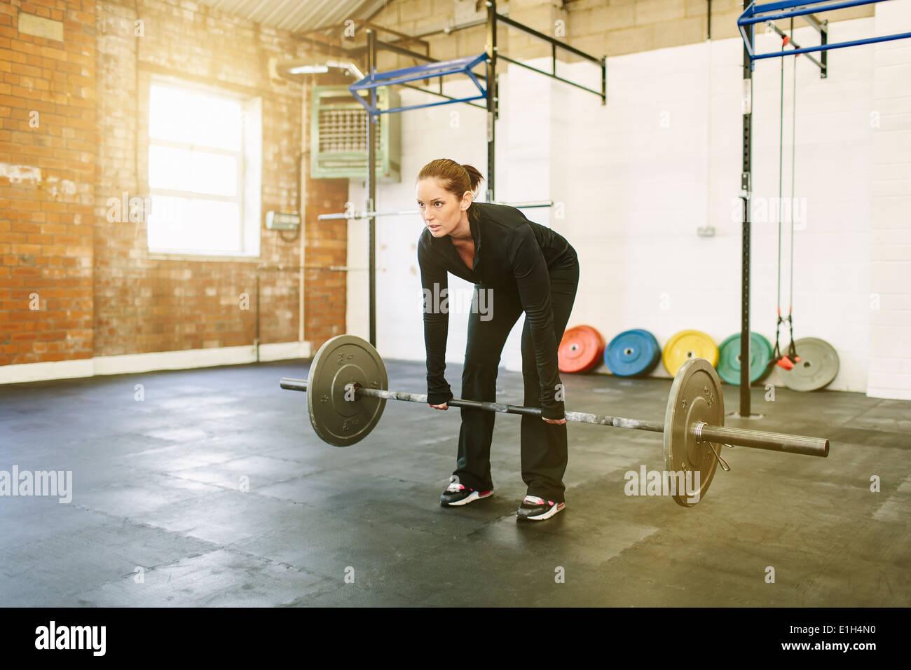 Frau heben Langhantel im Fitness-Studio Stockbild