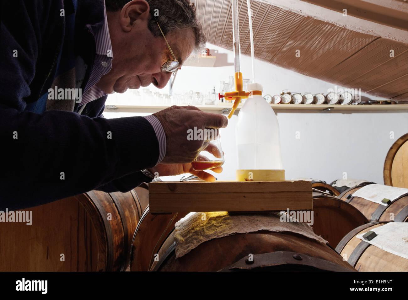 Mann macht und kümmert sich um über Aceto Balsamico Tradizionale di Modena Stockbild