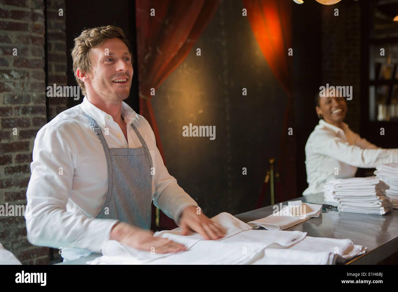 Koch und Kellnerin Falten Servietten im restaurant Stockbild