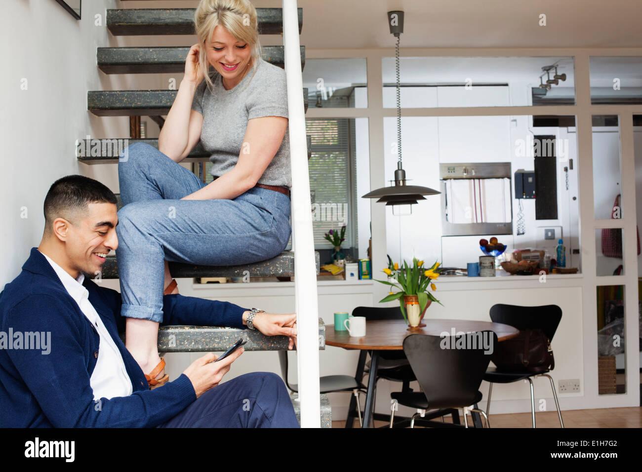Junger Mann und Frau sitzen auf Treppe, Blick auf smartphone Stockbild