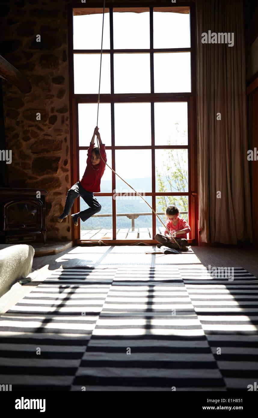 Zwei Geschwister in Wohnzimmer, Bruder am Seil und Schwester lesen Stockbild