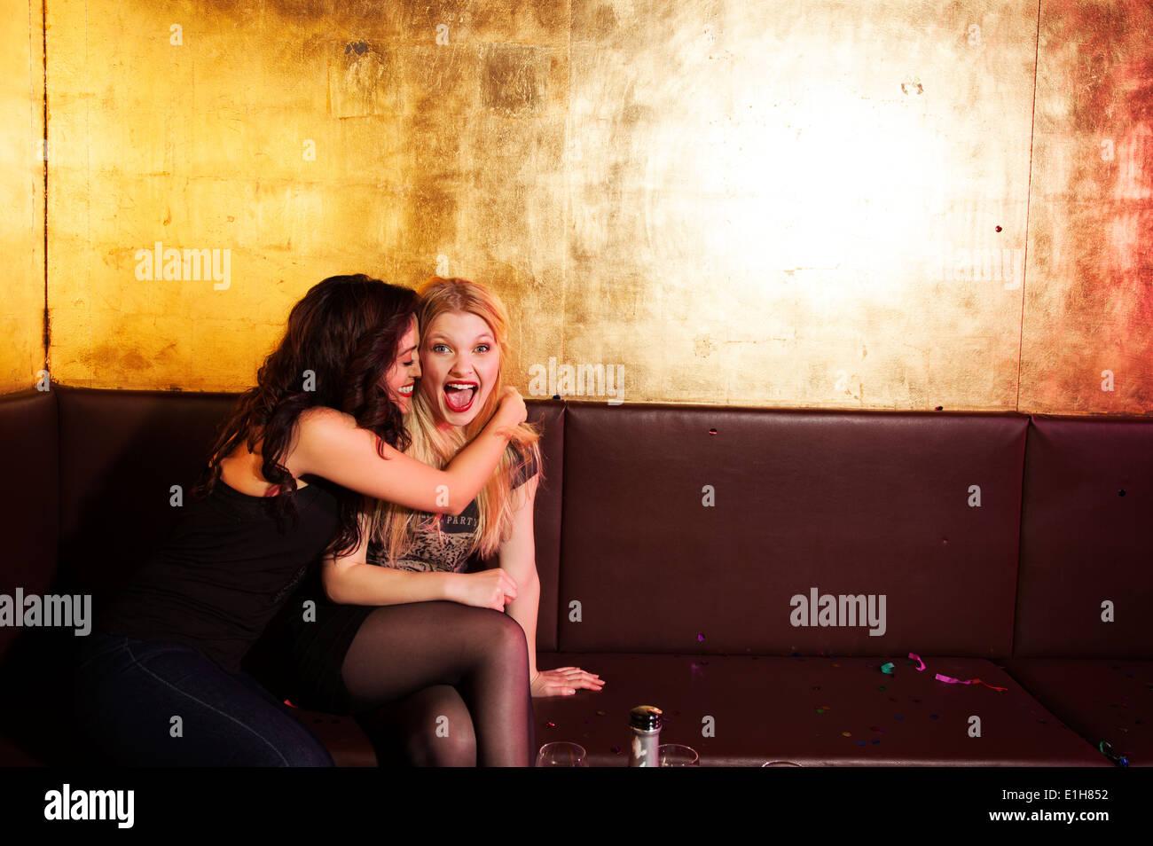 Zwei Freundinnen, die mit einem Lachen in Nachtclub Stockbild