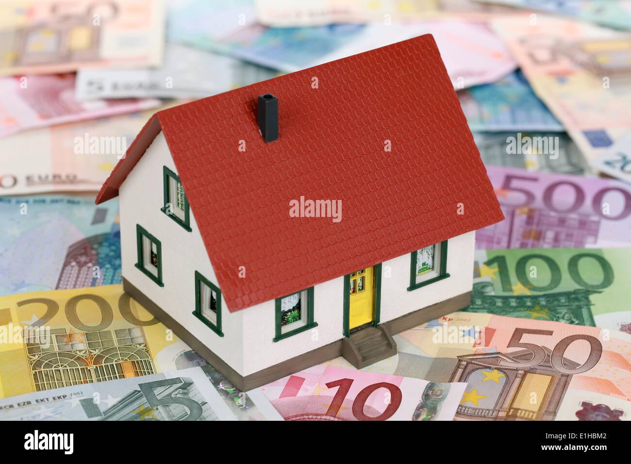 Symbol für Immobilienfinanzierungen mit einem Haus auf Euro-Banknoten Stockbild