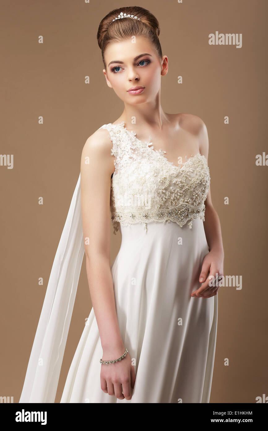Weiblichkeit. Sanfte Frau in Spitzen Kleid über Beige Hintergrund Stockbild