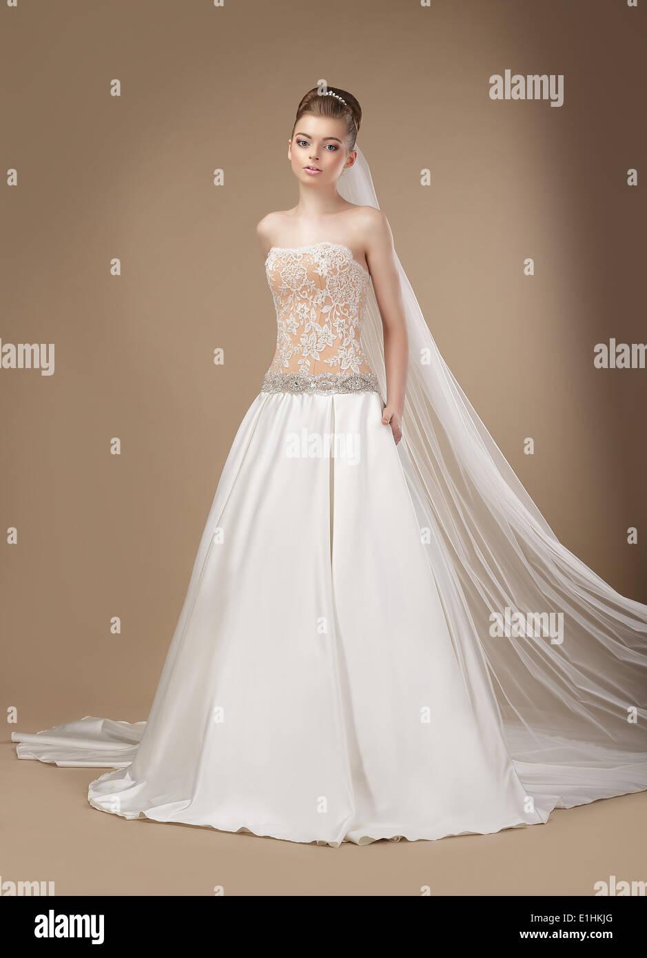 Luxus. Elegante klassische Brünette in Elfenbein leichten Kleid Stockbild