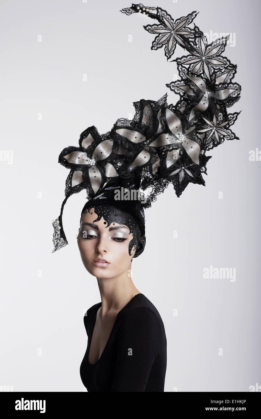 Fantasie. Surrealismus. Erstaunliche Frau in trendige Kopfbedeckung mit Blumen Stockfoto