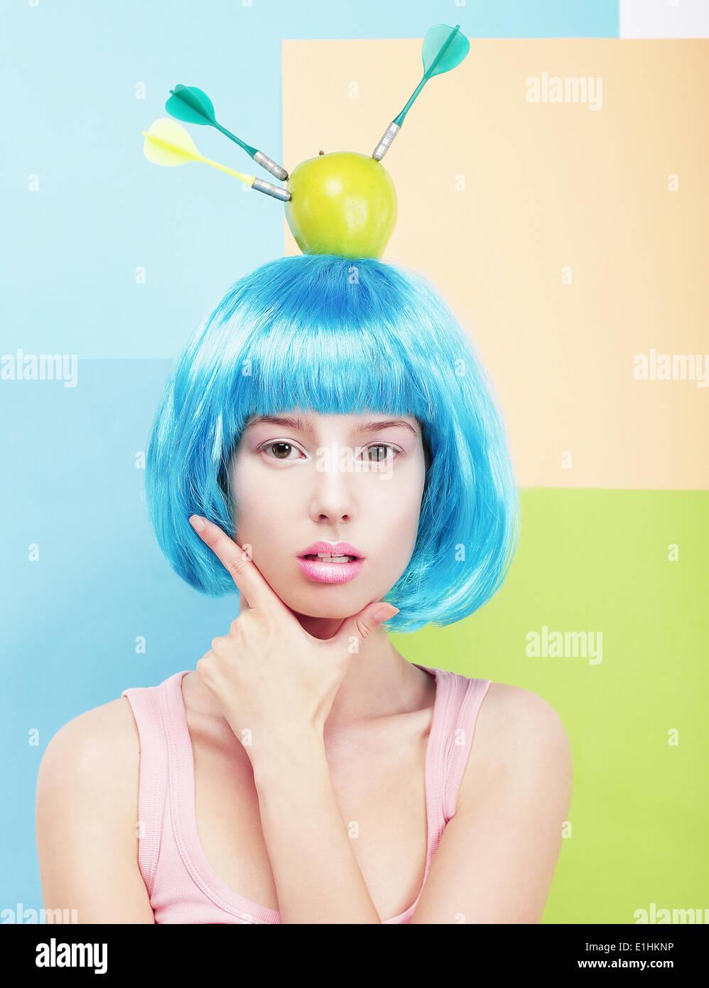 Kreativität. Frau mit blauen Haaren gemalt und Apfel auf den Kopf Stockbild