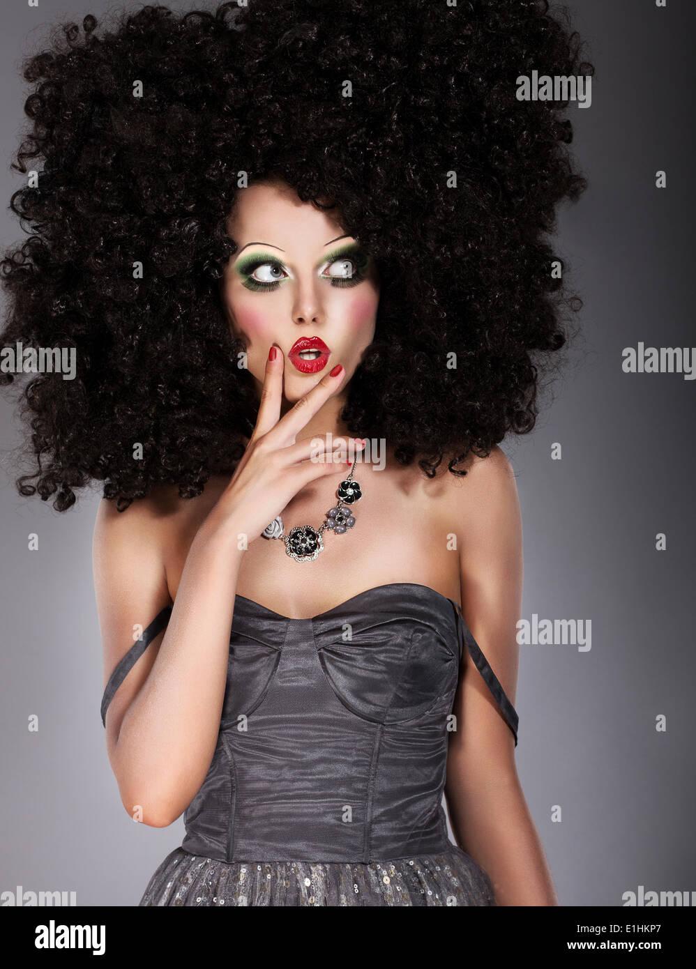 Vogue. Trendige Brünette in üppigen Kunst Perücke verzog das Gesicht. Kreativkonzept Stockbild