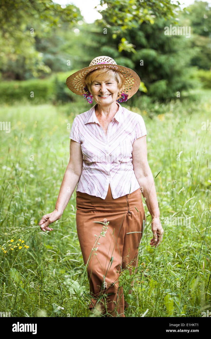 Gelassenheit. Freundlichen Senior Bäuerin im Stroh in der Wiese lächelnd Stockbild