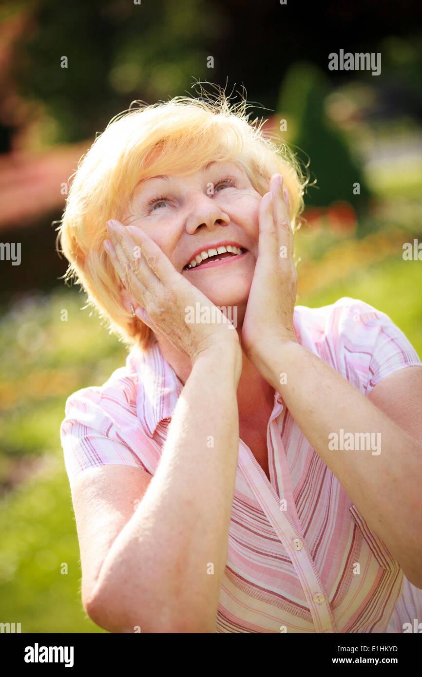 Hochgefühl. Ekstase. Überrascht mich grauhaarige Senior Woman nachschlagen Stockbild