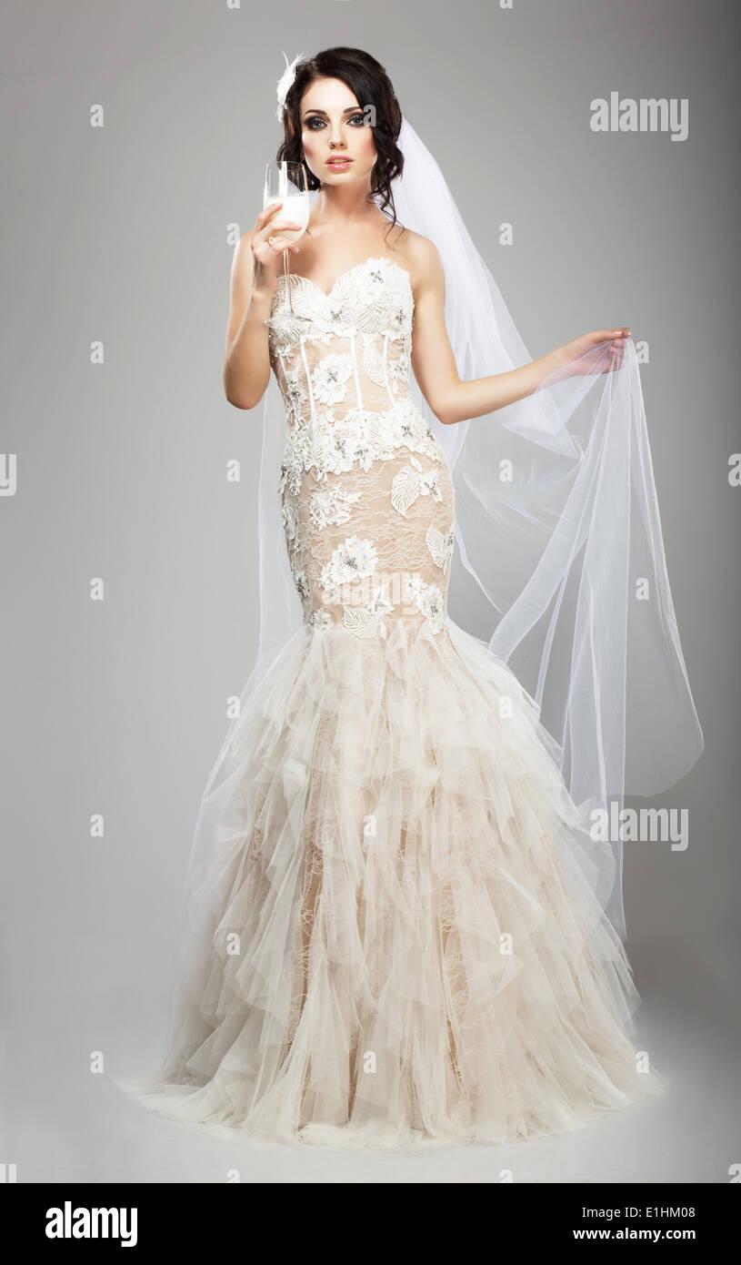 Modebewusste Frau im weißen Kleid mit Weinglas von Champagne Stockbild