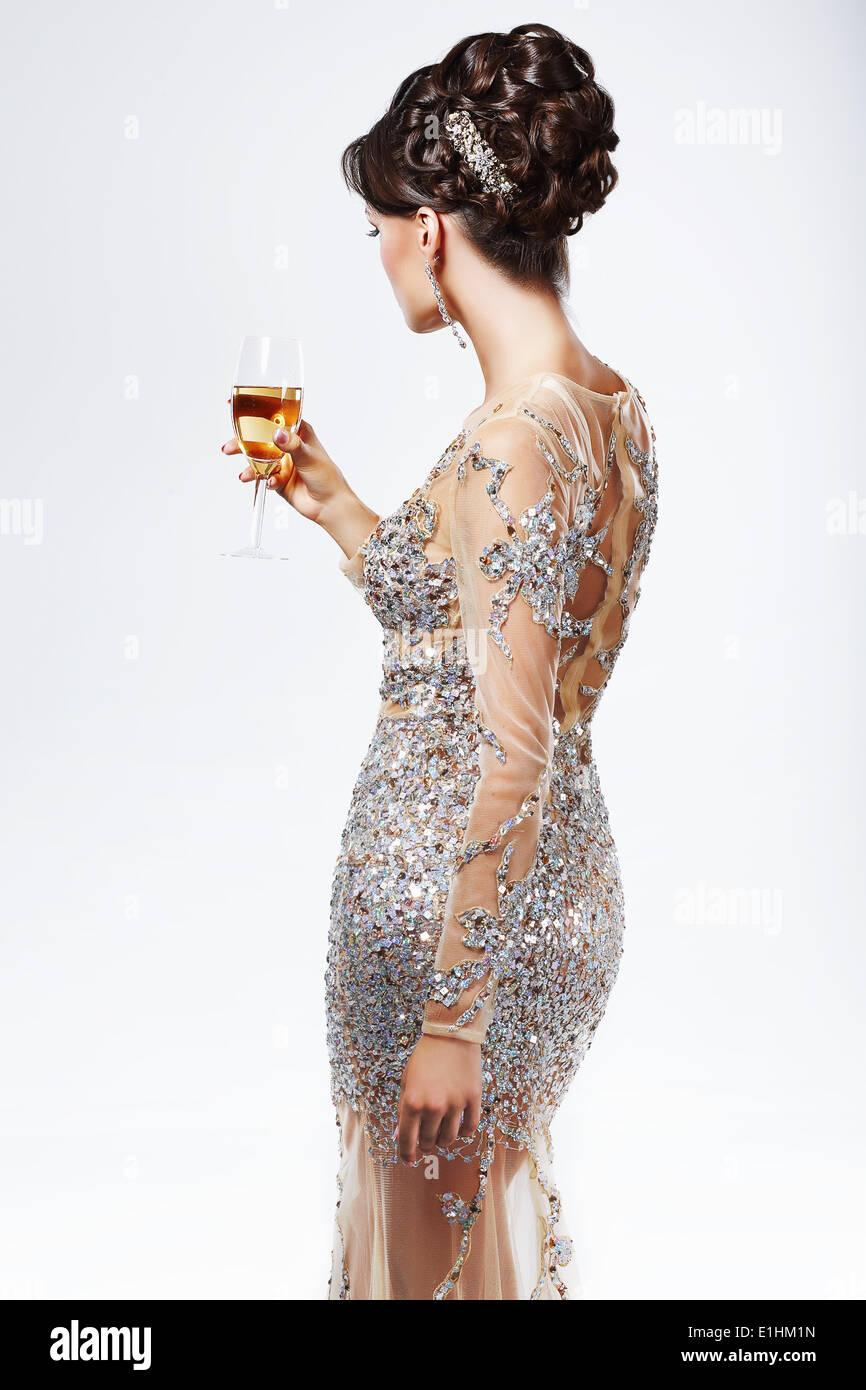 Elegante Dame in Silber-goldenes Kleid mit Weinglas von Champagne. Luxus Stockbild