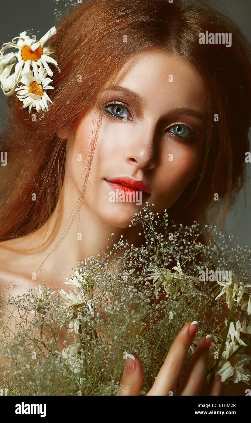 Pure Schönheit. Auburn Girl holding Bouquet von Wiesenblumen. Zärtlichkeit Stockfoto