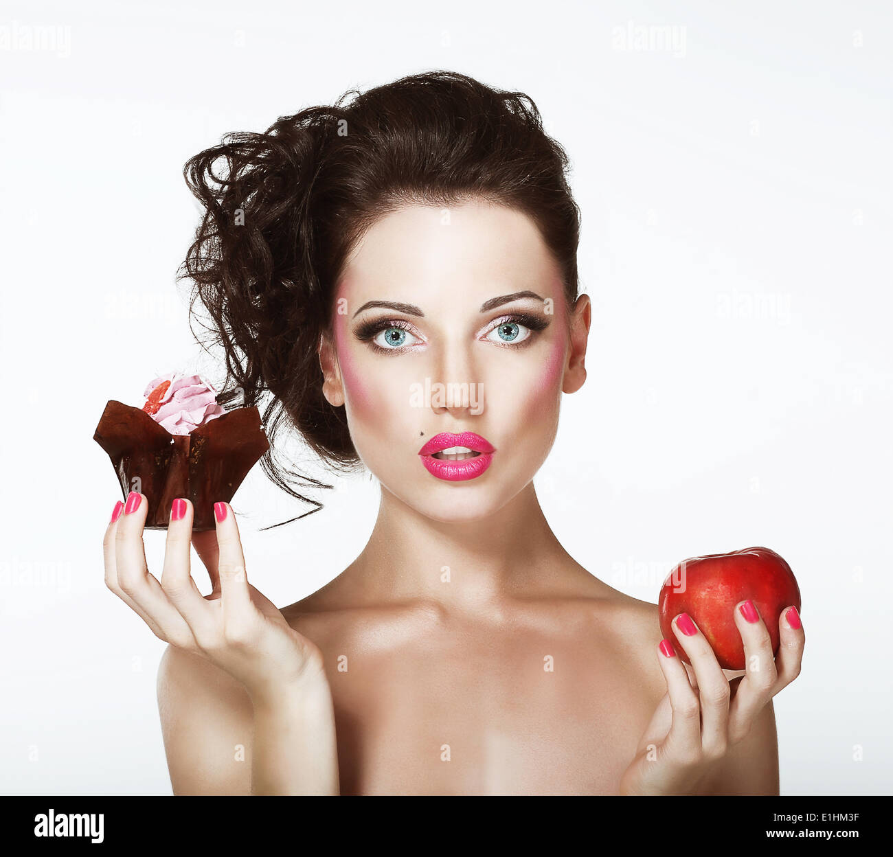 Dilemma. Ernährung. Unentschlossen Frau mit Apfel und Cupcake Stockbild