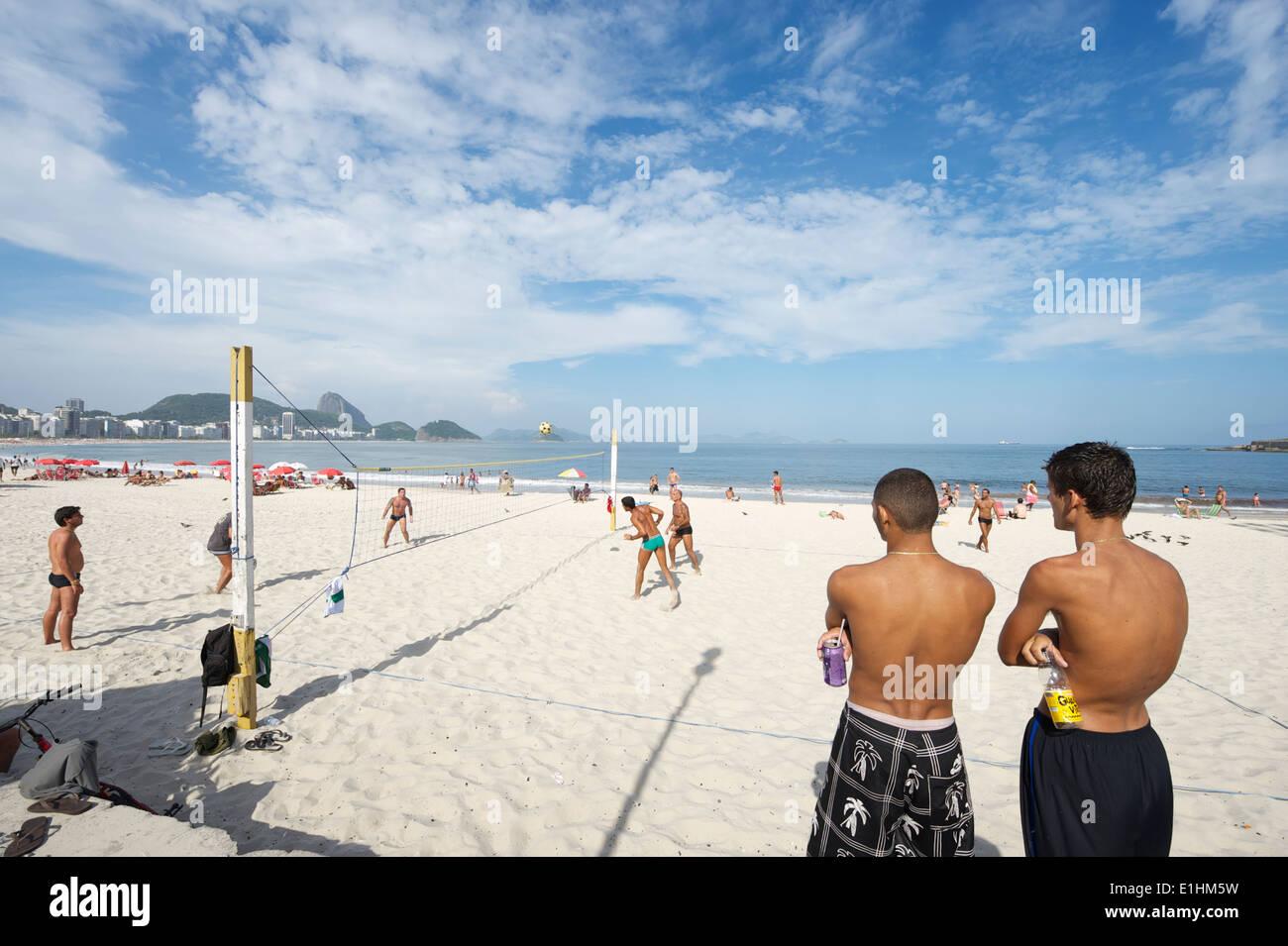 RIO DE JANEIRO, Brasilien - Januar 2011: Junge brasilianische Männer beobachten ein Spiel der Footvolley, ein Sport von Fußball und Volleyball. Stockfoto