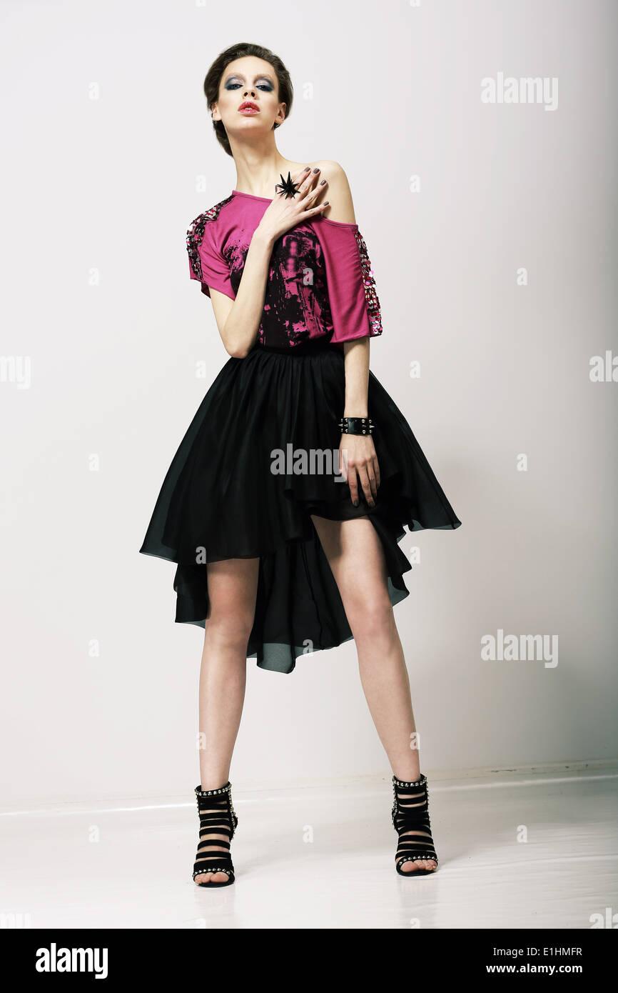 Tendenz. Glamouröse Mode-Modell in moderner Kleidung posiert im Studio Stockbild