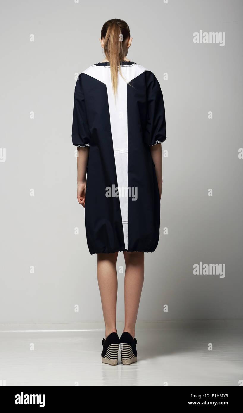 Rückansicht des trendigen Chichi Frau in weiß-schwarz-Kontrast Regenmantel. Vogue Stockbild