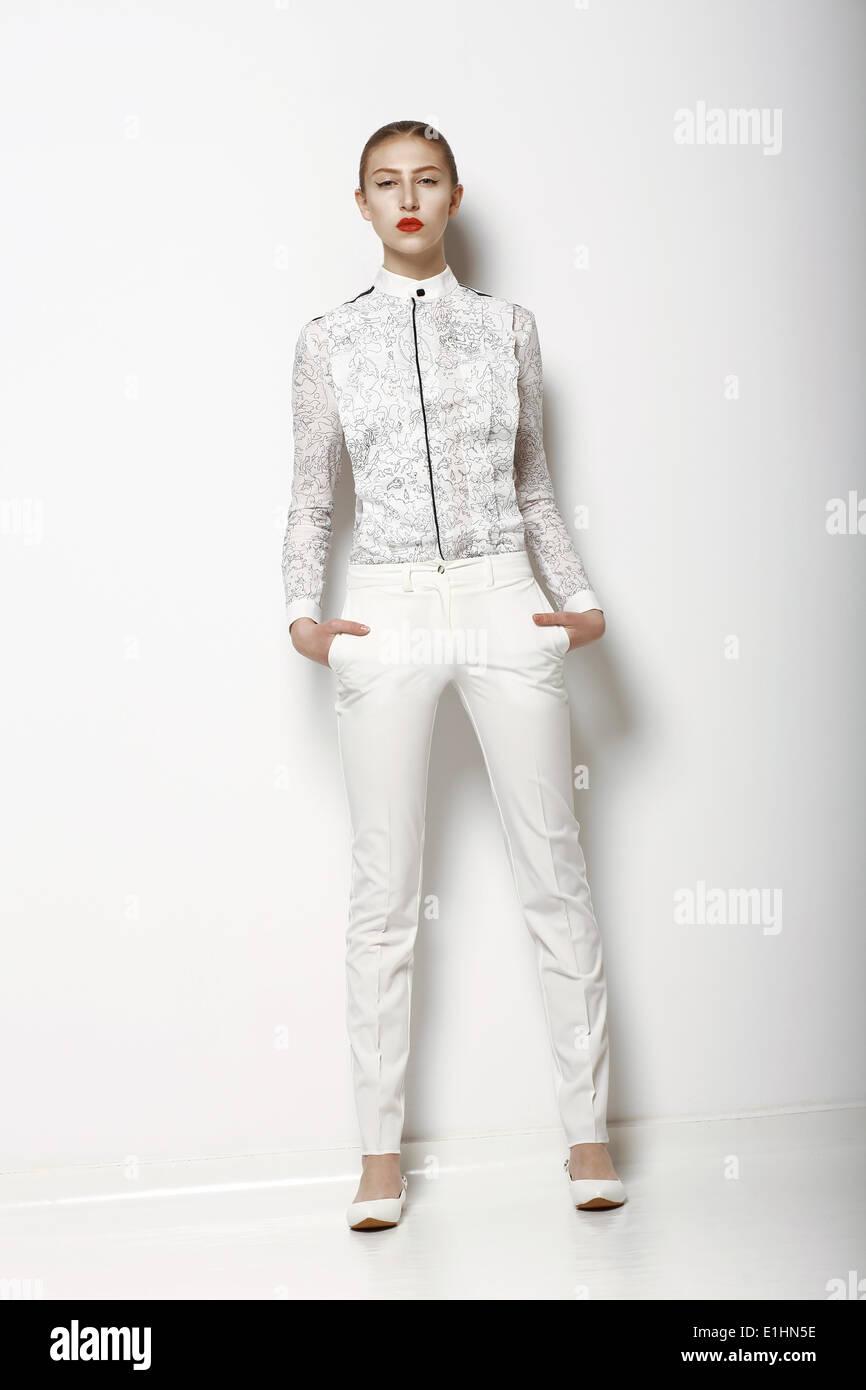 High-Fashion. Trendige Frau in weißen Hosen in anmutigen Pose. Frühjahrskollektion Zeit Stockbild