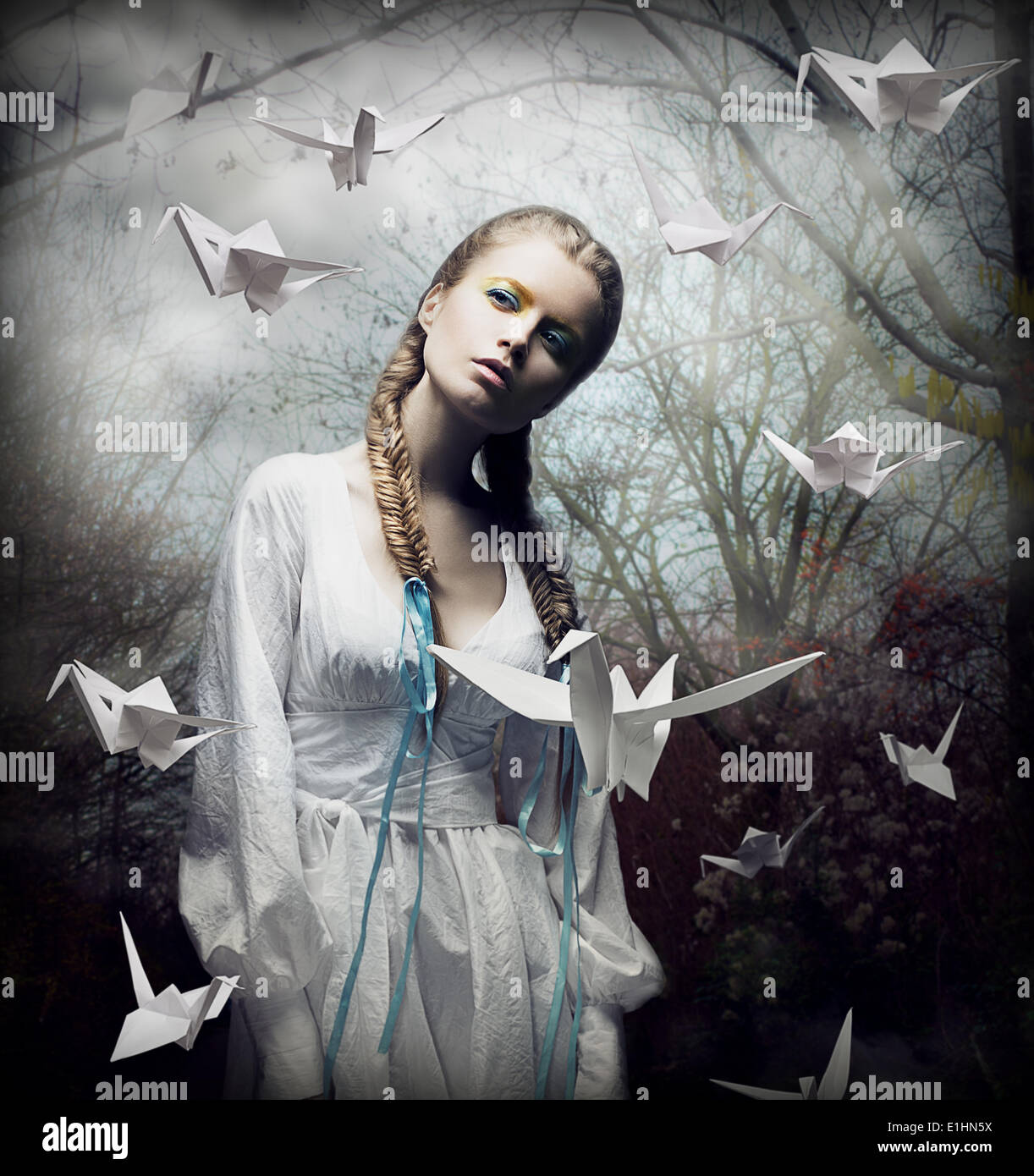 Phantasie. Romantische Blondine mit Origami-Vögel in gruseligen Wald schweben. Magie Stockbild
