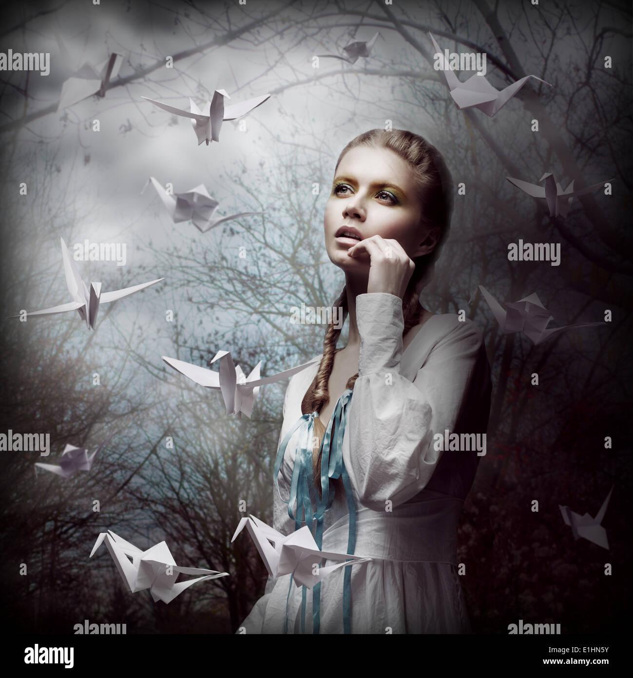 Inspiration. Frau mit fliegenden weißen Origami Schwäne in Dark Mystic Forest Stockfoto