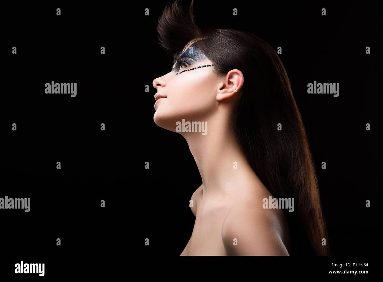 Glitzer. Profil von Brown Hair Woman mit blauen Lidschatten und Strass auf ihrem Gesicht Stockbild