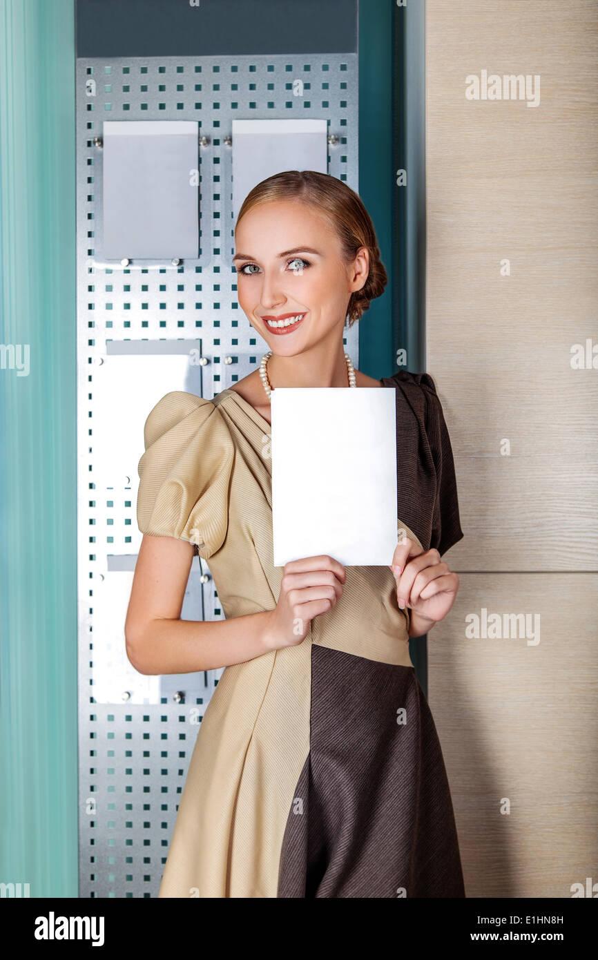 Lächelnde Geschäftsfrau hält ein weißes leeres Blatt Papier - Banner mit textfreiraum für text Stockbild