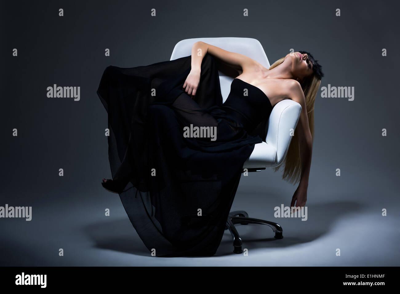 Harmonie & Sinnlichkeit. Romantische blonde Frau in schwarzes Kleid im Sessel ausruhen. Zufriedenheit Stockbild