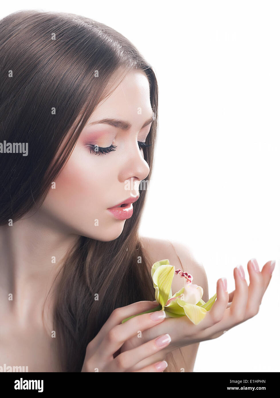 Junge schöne Frau Gesicht mit frischen Orchidee Blume close-up Portrait. Saubere, gesunde Haut Stockbild