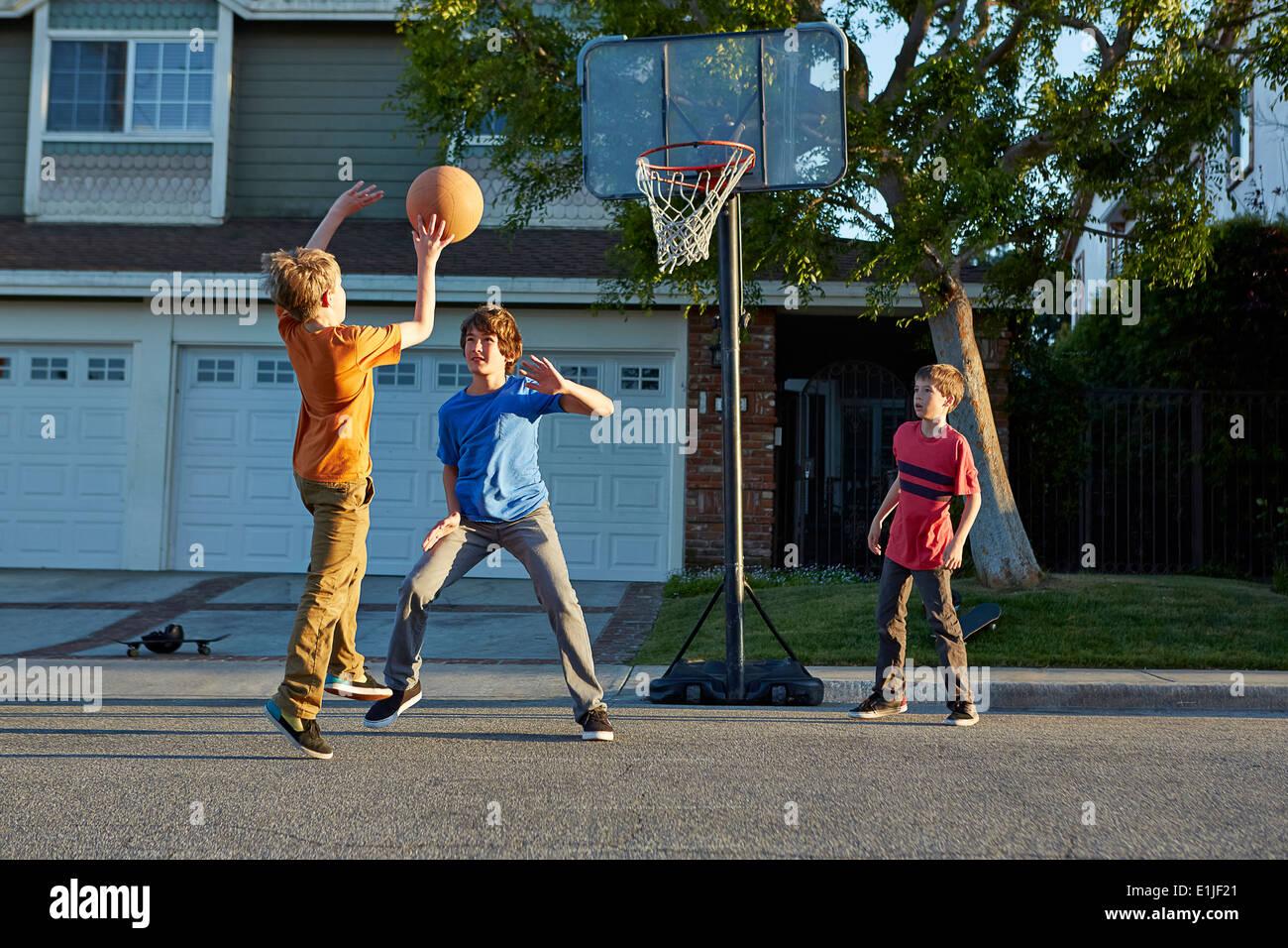 Jungen spielen Basketball vor Haus Stockfoto