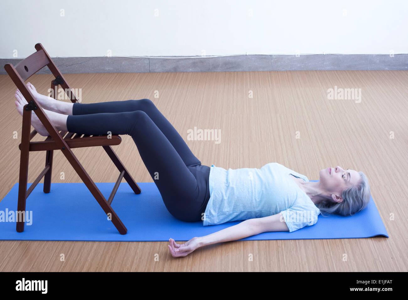Reife Frau, die Beine auf den Stuhl ruhen Stockbild