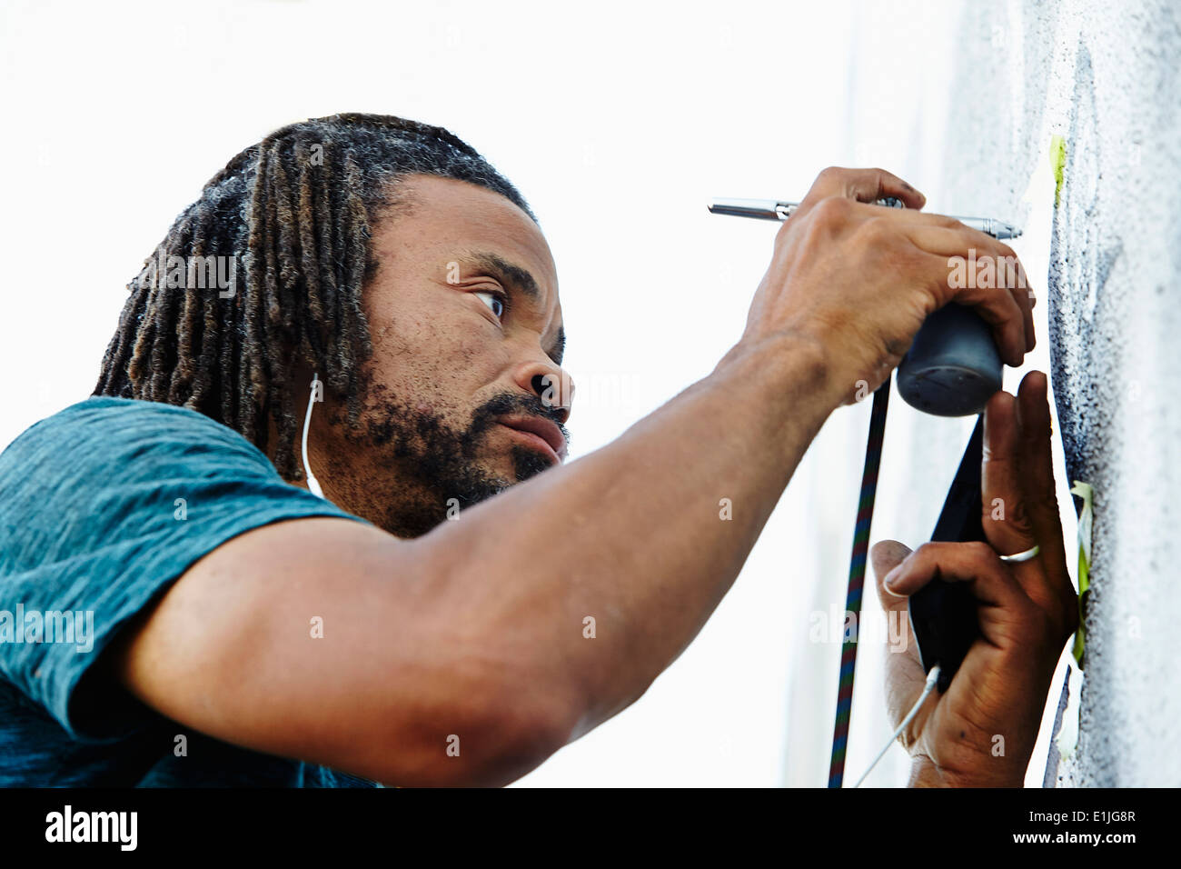 Nahaufnahme eines männlichen Afroamerikaner Airbrush Künstler Malerei Wandbild Stockbild