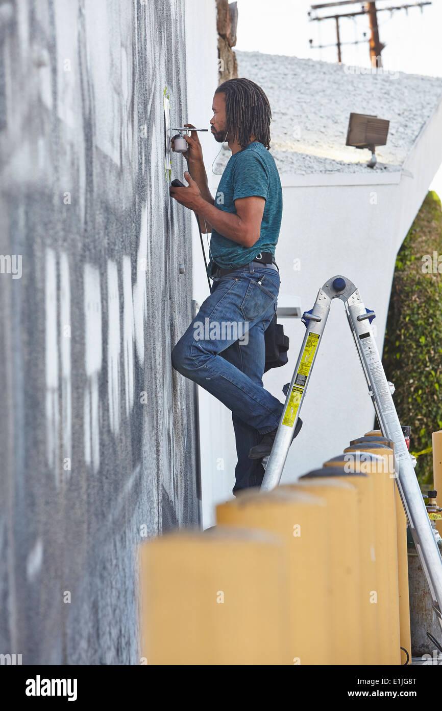 Männlichen Afroamerikaner Airbrush-Künstler auf Stehleitern Malerei Wandbild Stockfoto