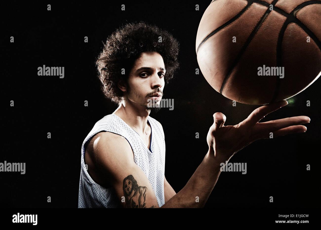 Basketball-Spieler Basketball am Finger zu balancieren Stockbild