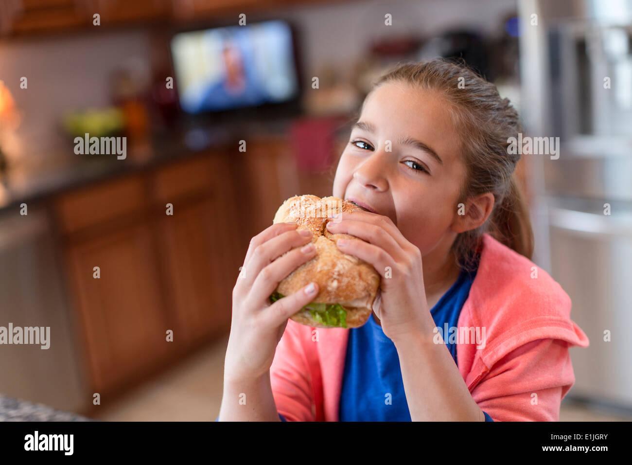 Mädchen in der Küche Sandwich beissen Stockbild