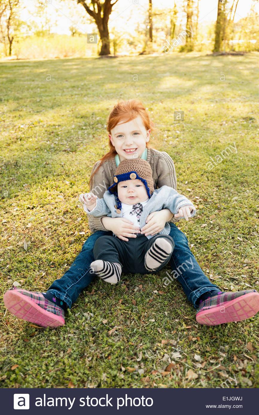 Porträt von Mädchen und Baby Bruder auf dem Rasen im park Stockbild