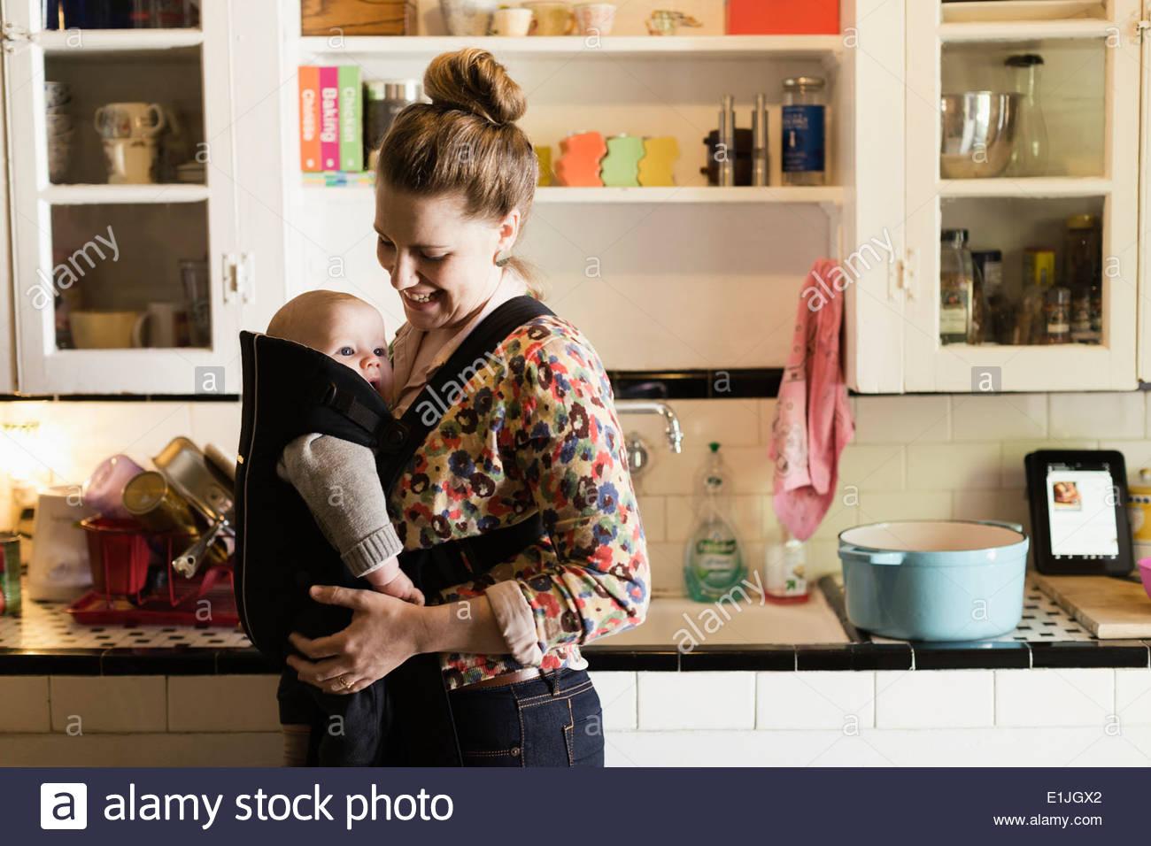 Mitte Erwachsene Mutter mit Baby Sohn in Schlinge in Küche Stockbild