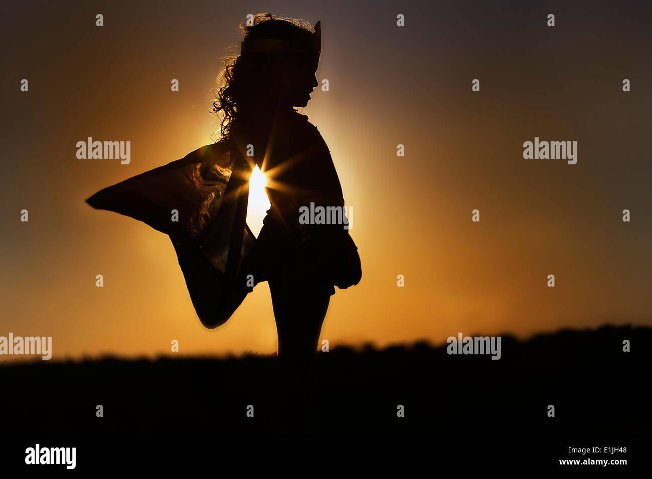 Silhouette eines jungen Mädchens in the Fairy Kostüm bei Sonnenuntergang Stockfoto